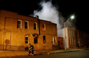 A Baltimore firefighter, who was the first emergency responder on the scene, approaches a fire set by rioters in a convenience store and residence on East Biddle Street and Montford Avenue during rioting in Baltimore, Maryland in the early morning hours of April 28, 2015.  REUTERS/Jim Bourg