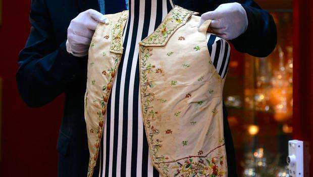 Julian Aalders from Aalders Auctions house adjusts a 250-year-old embroidered silk waistcoat that belonged to Captain James Cook on a mannequin during a display in Sydney, Australia, March 22, 2017.     REUTERS/David Gray
