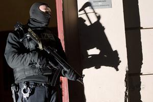 Special police force guards the entrance of a house in Berlin as police raids several residences in Berlin on suspicion of recruiting fighters and procuring equipment and funding for the so-called Islamic State terrorism group in Syria. Photo: AP