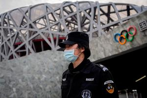 A security guard wearing a facemask outside the national 'Birds Nest' stadium, the site of the 2008 Beijing Olympics (Photo by NICOLAS ASFOURI/AFP via Getty Images)