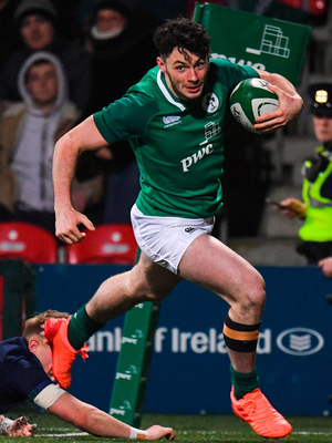 Andrew Smith of Ireland escapes the tackle of Roan Frostwick of Scotland. Photo: Harry Murphy/Sportsfile