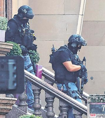 Armed police officers leave the Park Inn hotel in West George Street, Glasgow, where a man had been shot by an armed officer. Photo: Andrew Milligan/PA