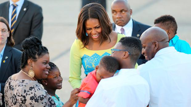 US first lady Michelle Obama greets a child as she arrives at Stansted Airport, Essex, for a visit to the UK, to promote her campaigns for girls' education and better support for military families. PRESS ASSOCIATION Photo. Picture date: Monday June 15, 2015. Mrs Obama, who is travelling with her mother and two daughters and arrives this evening, is due to meet Prince Harry and have tea at Downing Street with David and Samantha Cameron tomorrow. She will also host an event at the Mulberry School for Girls in Tower Hamlets in East London to discuss joint work between America and Britain to boost education for adolescent girls across the world through the Let Girls Learn initiative, championed by her and US president Barack Obama. After London, the party will fly on to Italy to meet US armed services families based in Europe and to visit the Milan Expo as part of the third strand of her work, encouraging healthier diets for children. See PA story POLITICS MichelleObama. Photo credit should read: Chris Radburn/PA Wire