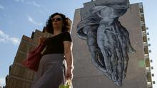 A woman walks past a mural of praying hands in Athens as the ruling Syriza party dismissed reform demands from the country's international creditors as 'blackmail' this week