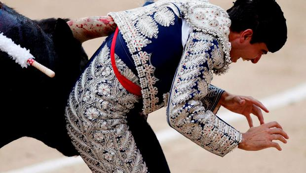 Spanish assistant bullfighter Marco Galan is tackled by a bull during a bullfight at the Ventas bullring in Madrid June 7, 2015.   REUTERS/Javier Barbancho