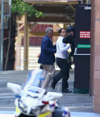 Two hostages run to safety outside the Lindt Cafe. Riot police watch on with weapons drawn. Photo: Mark Metcalfe/Getty Images