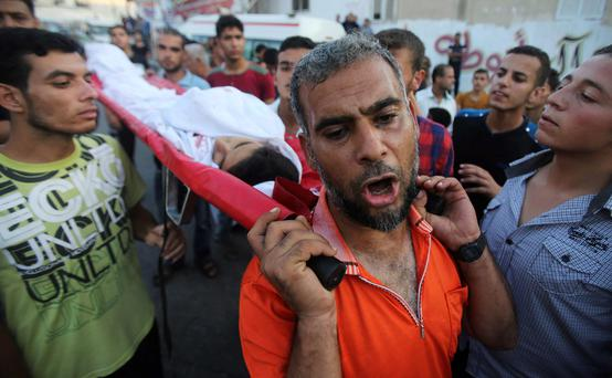 Mourners carry the body of Palestinian boy Mohammed Eweda , whom medics said was killed in an Israeli air strike, during his funeral in Rafah in the southern Gaza Strip. Reuters