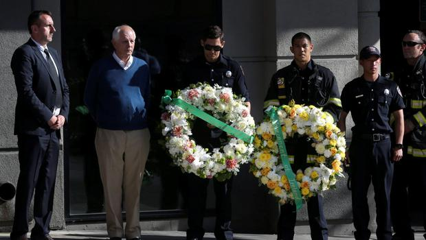 Berkeley Mayor Tom Bates (C) stands next to Philip Grant, Consul General of Ireland to the Western United States (L) and Berkeley Police officers before a wreath-laying ceremony at the scene of a 4th-story apartment building balcony collapse in Berkeley, California June 16, 2015. REUTERS/Elijah Nouvelage