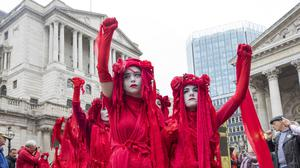 Protests: Financial institutions are being urged to address climate change, with  Extinction Rebellion activists dressed in red marching outside the Bank of England in London last month. Photo: Jason Alden