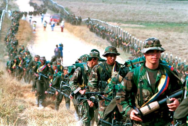 Leftist rebels of the Revolutionary Armed Forces of Colombia (FARC) patrol by a roadway near to San Vicente de Caguan January 9, 1999