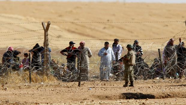 A Turkish soldier stands guard as Syrian refugees wait behind the border fences to cross into Turkey on the Turkish-Syrian border, near the southeastern town of Akcakale in Sanliurfa province, Turkey, June 5, 2015.REUTERS/Osman Orsal