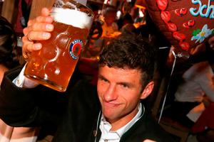 Bayern's Thomas Mueller lifts a glass of beer as the players of FC Bayern Munich visit the Oktoberfest beer festival 2015 at Theresienwiese in Munich, southern Germany, Wednesday, Sept. 30, 2015. (Alexander Hassenstein/pool via AP)