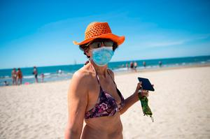A woman wearing a sunhat and protective face mask walks along the 'Couchant or Sunset beach' in La Grande Motte. (Photo by CLEMENT MAHOUDEAU / AFP) (Photo by CLEMENT MAHOUDEAU/AFP via Getty Images)