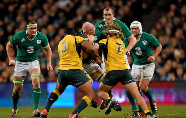 Paul O'Connell, Ireland, is tackled by Sekope Kepu, left, and Michael Hooper, Australia in the Guinness Series match