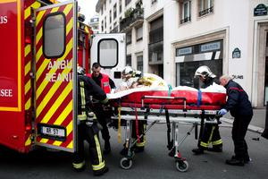 An injured person is transported to an ambulance after a shooting, at the French satirical newspaper Charlie Hebdo's office, in Paris. (AP Photo/Thibault Camus)