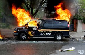 A police vehicle burns during unrest following the funeral of Freddie Gray in Baltimore. Photo: AP