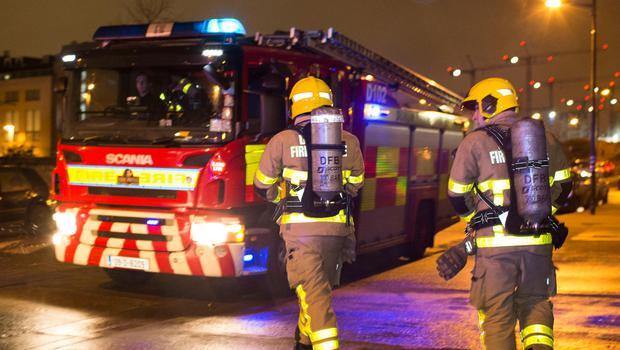 Fire fighters return to their tender after dealing with an incident whereby a domestic cooking accident had triggered a fire alarm  in an apartment complex near Ringsend, Dublin. Photo: Conor O Mearain