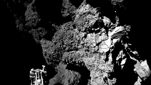 Rosetta's lander Philae safely on the surface of Comet 67P/Churyumov-Gerasimenko, with one of the lander's three feet in the foreground, as scientists  re-established communication with the Philae space probe, which has made history by landing on the comet