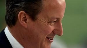 Britain's Prime Minister David Cameron smiles as he arrives for the general election count in Witney, Britain May 8, 2015