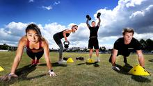 Working out: Agape Deng (left) from Rathmines and Claire Arnold (back) from Ranelagh, exercising with Ronan Mahon of Movement Fitness (centre) and co-owner Mark Ward (right) at Leinster Cricket Club. Photo: Steve Humphreys
