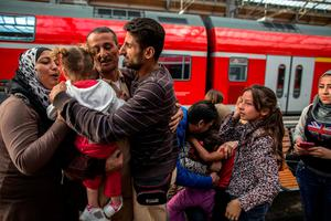 Ihab, 30 (C), a Syrian migrant from Deir al-Zor, cries as he and his family are welcomed by his relatives upon their arrival at the railway station in Lubeck, Germany September 18, 2015.EUROPE-MIGRANTS/JOURNEY REUTERS/Zohra Bensemra/Files
