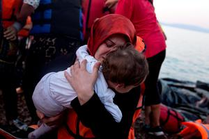 A Syrian woman holds her child after they arrive aboard a dinghy  from Turkey, to the island of Lesbos, Greece, on Saturday, Sept. 19, 2015. (AP Photo/Petros Giannakouris)