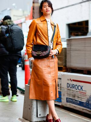 A guest is seen wearing a dark yellow coat, white shirt, brown skirt, black purse and maroon heels outside of the Coach 1941 show during New York Fashion Week on February 11, 2020 in New York City. (Photo by Donell Woodson/Getty Images)
