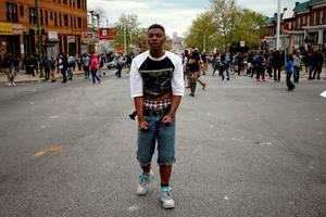 A demonstrator stands on the street after throwing rocks at the Baltimore police during clashes in Baltimore, Maryland. Photo: Reuters