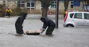Residents struggle through floodwater in Egham, Surrey. Photo: Steve Parsons/PA Wire