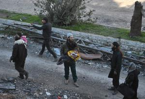 Civilians are helped out of the besieged district of the central Syrian city of Homs, ahead of being evacuated by United Nations (UN) staff to a safer location, on February 9, 2014.
