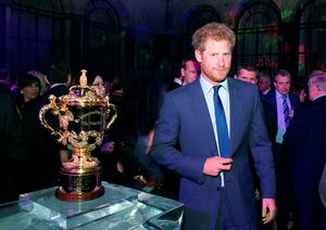 Britain's Prince Harry, honorary president of England Rugby 2015, stands next to the Webb Ellis trophy as he attends the Rugby World Cup Official Welcome Party, hosted by the Rugby Football Union (RFU), at the Foreign and Commonwealth Office in central London