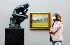 "A visitor wearing a face mask looks at French sculptor Auguste Rodin's iconic sculpture ""The Thinker"" at the Alte Nationalgalerie (Old National Gallery) museum in Berlin  (Photo by JOHN MACDOUGALL/AFP via Getty Images)"