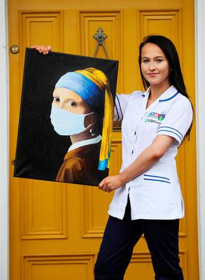 Work of art: Chloe Slevin, a first-year children's and general nurse trainee, currently working on a Covid-19 ward at St Vincent's Hospital in Dublin as a healthcare assistant, with her painting 'Girl With A Surgical Mask' which she is hoping to auction in aid of the Feed the Heroes charity. PHOTO: BRIAN LAWLESS/PA WIRE