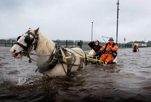 A local man and his horse ferries people in and out of Saint Marys Park in Limerick after the River Shannon burst its banks in Limerick City in another wave of storms to hit the city