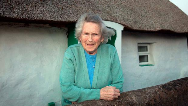 Kathleen Byrne outside her thatched cottage in Raheny. Photo: Collins