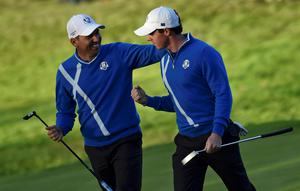 European Ryder Cup player Rory McIlroy (R) is congratulated by teammate Sergio Garcia after winning the hole on the 17th green during their foursomes 40th Ryder Cup match at Gleneagles in Scotland (REUTERS/Toby Melville)
