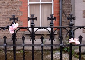 General view of baby shoes tied to railings of former Magdalene Laundry (Our Lady of Charity Refuge) ahead of Say No to The Pope and Stand4Truth protest. Sean McDermott Street, Dublin. Picture: Caroline Quinn