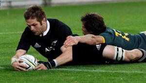 Richie McCaw (L) of New Zealand's All Blacks scores a try against South Africa's Springboks Jan Serfontein during their Rugby Championship match at Westpac Stadium in Wellington