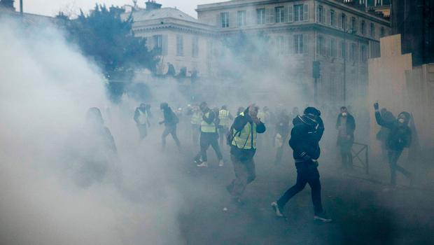 Demonstrators run as tear gas is thrown by riot police during a protest in Paris, Saturday, Jan. 5, 2019. Hundreds of protesters were trying to breathe new life into France's apparently waning yellow vest movement with marches in Paris and gatherings in other cities. (AP Photo/Kamil Zihnioglu)