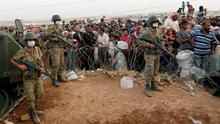 Turkish soldiers stand guard as Syrian Kurdish refugees wait behind the border fences to cross into Turkey near the southeastern town of Suruc in Sanliurfa province. Militants still held their positions around 10 kilometres west of Kobane inside Syria, a witness said, with Kurdish positions the last line of defence between the fighters and the town. Kobane sits on a road linking north and northwestern Syria and Kurdish control of the town has prevented Islamic State fighters from consolidating their gains, although their advance has caused more than 150,000 Kurds to flee to Turkey since last week