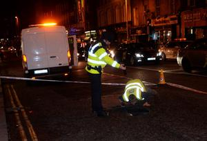 General view of Gardai and council workers at scene of ground hole. Dame Street, Dublin