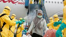 Epidemic: Officials in protective gear disinfect Indonesian students as they disembark on arrival at Hang Nadim international airport in Batam, following their evacuation from the Chinese city of Wuhan. Photo: AFP via Getty Images