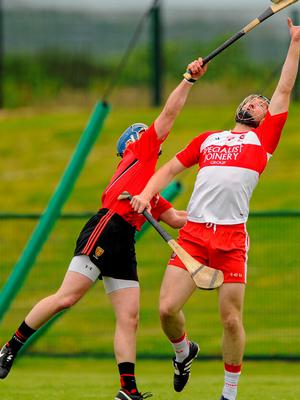 Conor Quinn of Derry battles Down's Danny Toner for control of the sliotar