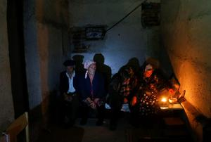Local residents sit in a basement used as a shelter from artillery fire, in the village of Spartak, on the outskirts of Donetsk