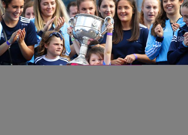 29/9/2019, Sophie Mcdonagh lifts the Brendan Martin Cup with the Dublin Ladies team at the homecoming for the winning All Ireland Ladies and Mens teams at Merrion square, Dublin.  Picture credit; Damien Eagers / INM
