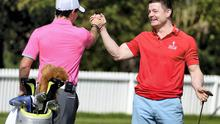 Rory McIlroy congratulates Brian O'Driscoll during the Pro-Am event in Abu Dhabi yesterday