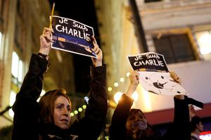 Two woman raise signs during a vigil outside the Consulate General of France to pay tribute to the victims of an attack on satirical magazine Charlie Hebdo in Paris, in San Francisco, California January 7, 2015. REUTERS/Stephen Lam