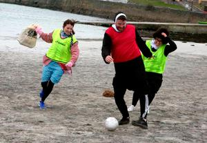 Lindsay Markey and Anita Looby chase Jimmy Kelly with shopping bags during a game of football at the Fr Ted festival on Inis Mór. Photo: Hany Marzouk
