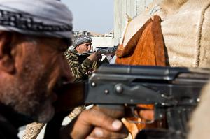 In this Wednesday, Nov. 19, 2014 photo, fighters from the Free Syrian Army, left, and the Kurdish People's Protection Units (YPG), center, join forces to fight Islamic State group militants in Kobani, Syria. (AP Photo/Jake Simkin)