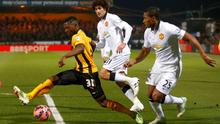 Manchester United's Antonio Valencia (R) and Marouane Fellaini (C) challenge Cambridge United's Sullay Kaikai during their English FA Cup 4th round match